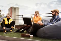 Hipster office team, creative coworking. Use and typing on laptop, outside