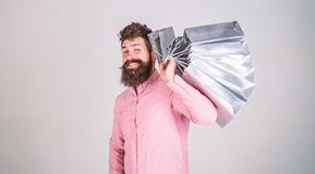 Free Hipster On Winking Face Shopping. Guy Shopping On Sales Season, Carries Bunch Of Bags On Shoulder. Man With Beard And Royalty Free Stock Photos - 137826318