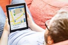Hipster op de bank met de tablet van het restaurantonderzoek Royalty-vrije Stock Afbeelding
