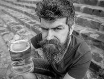 Hipster op strikt gezicht het drinken bier openlucht, omhoog opheffend drank Juicht concept toe De mens met baard en snor houdt g royalty-vrije stock afbeeldingen