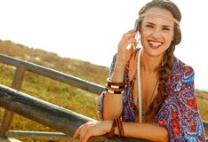 Hipster outdoors in summer evening speaking on cell phone. Bohemian vibe vacation. Portrait of smiling trendy hipster in jeans shorts and cape outdoors in the Royalty Free Stock Photography