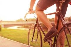 Hipster på cykeln i staden på solnedgången arkivbild