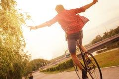 Hipster på cykeln på staden i solnedgång royaltyfria bilder