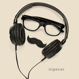 Hipster. A pair of glasses, a mustache and a pair of headphones, and the word hipster on a beige background royalty free stock photos