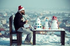 Hipster with pencil and notebook sitting on chair. Santa man writing on winter day. Christmas and new year holidays celebration. Snowmen and snow xmas tree on stock image
