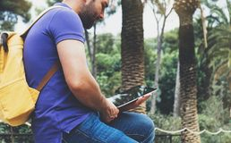 Hipster person holding in hands digital tablet with blank screen, man reading on computer on background nature park palm landscape. Mock up technology blur royalty free stock image