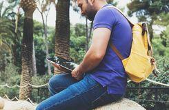 Hipster person holding in hands digital tablet with blank screen, man reading on computer on background nature park palm landscape. Mock up technology blur royalty free stock photo