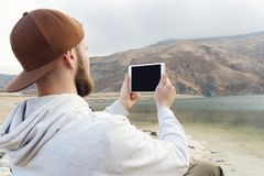 Hipster person holding in hands digital tablet with empty blank screen, man photograph on computer on background nature Stock Photos