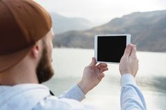 Hipster person holding in hands digital tablet with empty blank screen, man photograph on computer on background nature Royalty Free Stock Photos