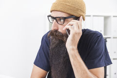 Hipster on the phone. Close up of hipster with long beard wearing glasses and a beanie who is on his phone in office with white walls royalty free stock photography