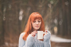 Hipster. Photo redheaded girl with a cup in his hand. Royalty Free Stock Photography