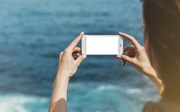 Hipster photograph on smart phone gadget mobile, mock up of blank screen. Traveler hold and using in female hand mobile on back royalty free stock photography