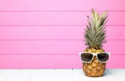Hipster pineapple with sunglasses against pink wood. Hipster pineapple with sunglasses against a pink wooden background Stock Photo