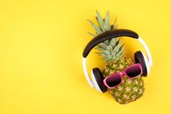 Hipster pineapple with sunglasses and headphones over a yellow background. Hipster pineapple with sunglasses and headphones. Top view against a yellow background stock photo
