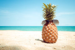 Hipster pineapple with sunglasses on a sandy at tropical beach. royalty free stock image