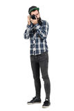 Hipster in plaid shirt taking photo with dslr camera looking at camera. Royalty Free Stock Image