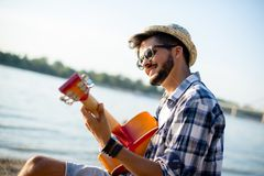Hipster is playing guitar on the beach. In sunset Stock Photos
