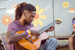 Hipster playing guitar for his friends Royalty Free Stock Images