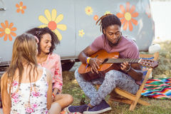 Hipster playing guitar for his friends Royalty Free Stock Photography