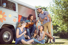 Hipster playing guitar for his friends Royalty Free Stock Photos