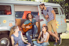 Hipster playing guitar for his friends Royalty Free Stock Image