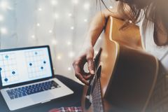 Hipster playing guitar in home atmosphere, person studying on musical instrument, notes in laptop on background glow bokeh royalty free stock photos