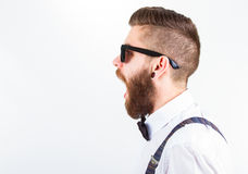 Hipster portrait. Profile  of a young hipster man wearing elegant clothes and eyeglasses with open mouth Stock Photo
