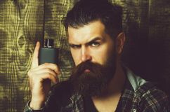 Hipster posing with black perfume or cologne bottle. Hipster or brutal caucasian man with grey hair, long beard and moustache posing with black perfume or stock photos
