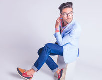 Hipster posing seated with legs crossed while touching his neck Royalty Free Stock Photos