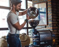 Hipster pouring raw coffee beans in a coffee roaster. Smiling hipster man pouring raw coffee beans in a coffee roaster Royalty Free Stock Photography