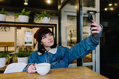 Hipster pretty girl sitting in a cafe and posing for the camera of your phone. Hipster pretty girl sitting in a cafe drinking a hot drink and posing for the Stock Photography