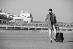 Hipster ready enjoy travel. Carry travel bag. Man bearded hipster travel with luggage bag on wheels. Traveler with stock image