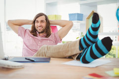 Hipster realaxing with legs on desk Stock Photography