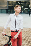 Hipster with red bycicle and tattoo on leg Stock Photos