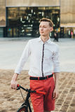 Hipster with red bycicle and tattoo on leg Royalty Free Stock Photos