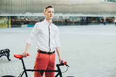 Hipster with red bycicle and tattoo on leg Stock Images