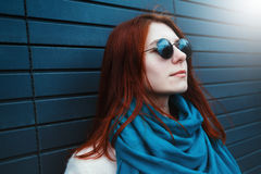 Hipster redhaired girl in stylish sunglasses is posing in front of a black wall on the street Royalty Free Stock Photos