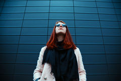 Hipster redhaired girl in stylish sunglasses is posing in front of a black wall on the street Stock Images