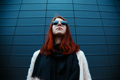 Hipster redhaired girl in stylish sunglasses is posing in front of a black wall on the street Stock Photo