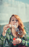 Hipster redhead girl blowing bubbles Stock Image