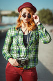 Hipster redhead girl in hat and sunglasses with retro camera Royalty Free Stock Photo