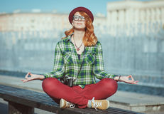 Hipster redhead woman in hat and glasses doing yoga on the bench Royalty Free Stock Photos