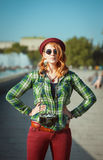 Hipster redhead woman in hat and glasses with retro camera Stock Image