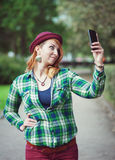 Hipster redhead woman in hat taking picture of herself Royalty Free Stock Images