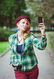 Hipster redhead woman in hat taking picture of herself Stock Images