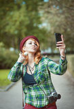 Hipster redhead woman in hat taking picture of herself Stock Image