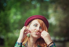 Hipster redhead woman making a moustache with her hair stock images