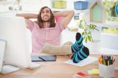 Hipster relaxing with legs on desk Stock Photo