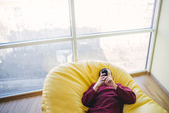 Hipster resting in a bad chair. The young man is and uses smartphone. Modern office. Man in modern interior. Hipster bag resting in a chair. The young man is Stock Photo