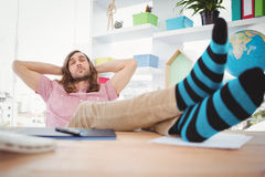 Hipster resting with legs on desk in office Royalty Free Stock Photo